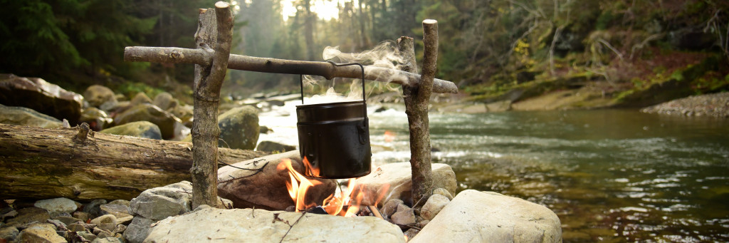 Cooking on bonfire. Campfire near mountain river. Camping fire on the river bank. Concept travel, hiking and adventure.