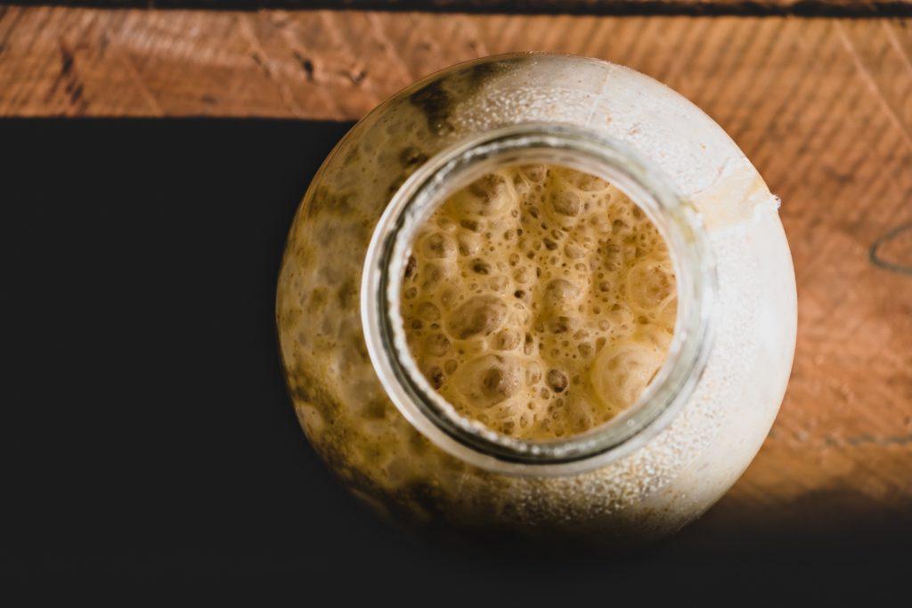 Ein Sauerteig im Glas angesetzt, gärt und bildet Blasen, von oben gesehen