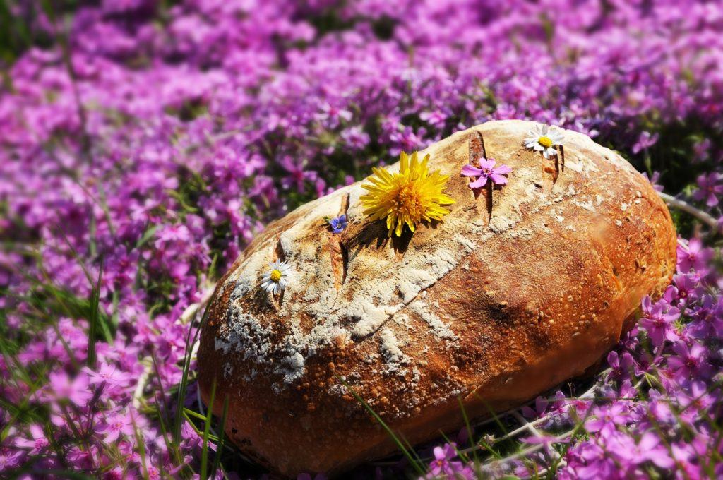 Sauerteigbrot in der Natur, auf lila blühender Wiese mit einigen Blüten verziert