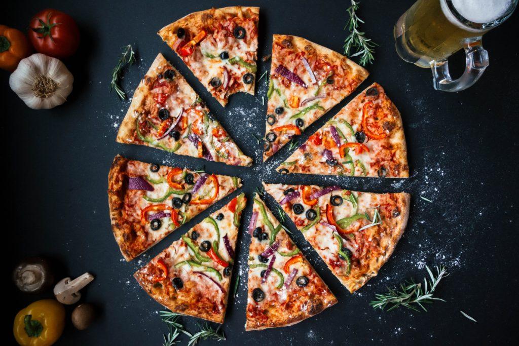 bunt belegte Pizza mit Zwiebeln, Olliven, Paprika auf schwarzem Untergrund mit Gewürzen und Bier an der Seite ein Bier