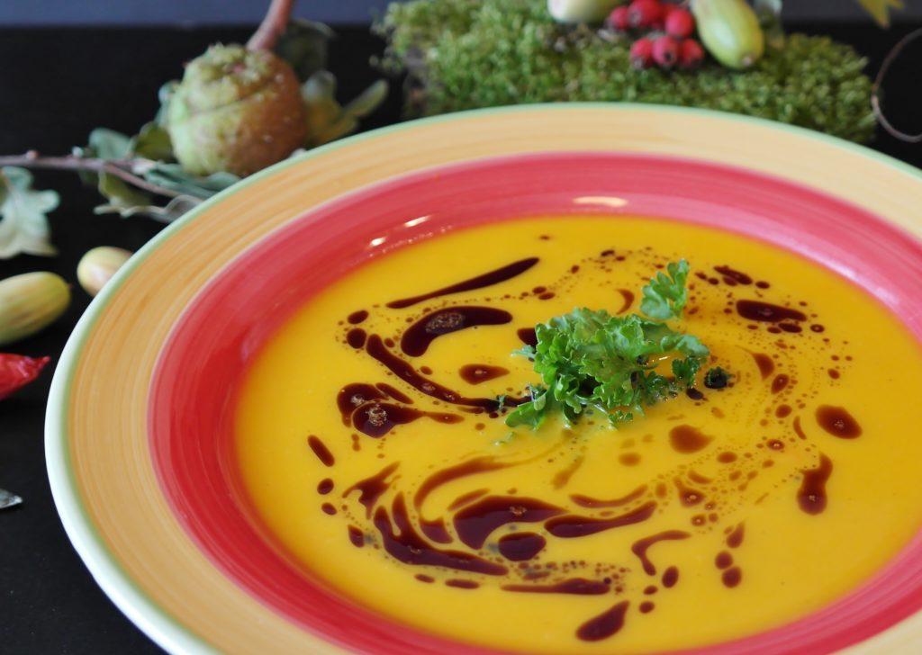 kürbissuppe mit Balsamicoschlieren und Petersilie in einem hell-pink Teller