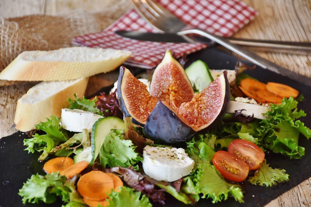 Salat mit Feige, Käse, Tomate, Karotte auf schwarzer Platte angerichtet mit Baguette un drot weißer Serviette