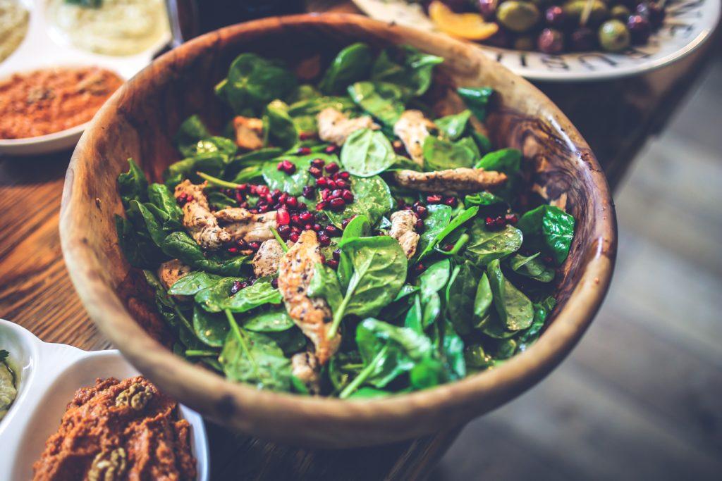 Salatschüssel aus Holz, Spinat, angebratenes Hühnchen und Dips drum herum
