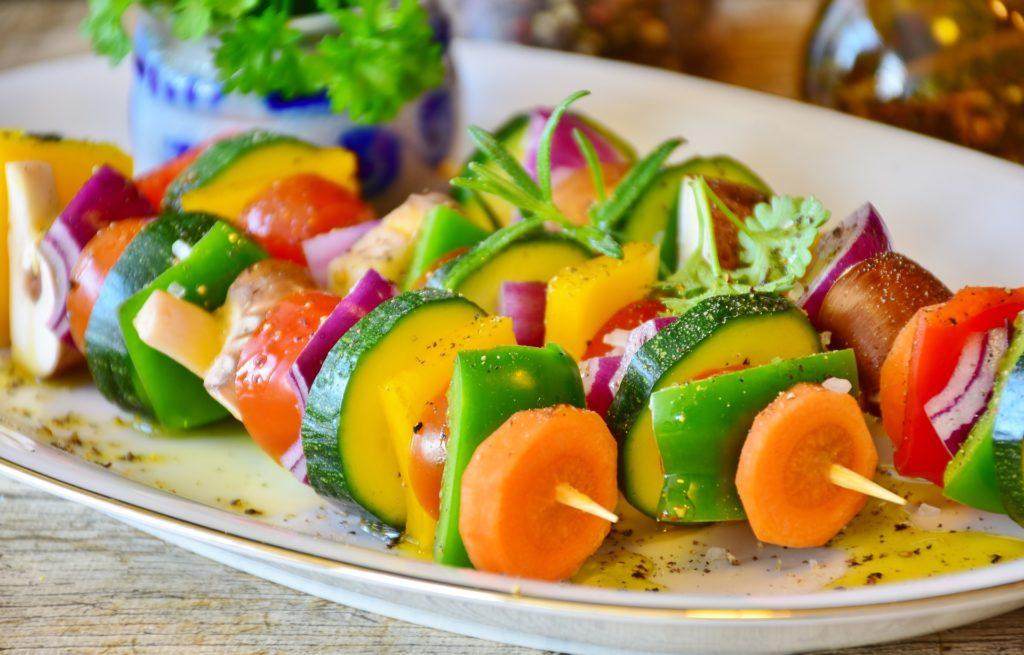 Gemüsespieß aus Karotte, Zucchini, grüner Paprika, roter Paprika und Rosmarin. Auf weißer Platte angerichtet
