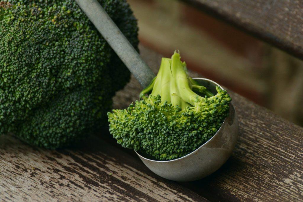 Brokkoli rose in einer Suppenkelle, dahinter großer Brokkoli auf Holzbrett