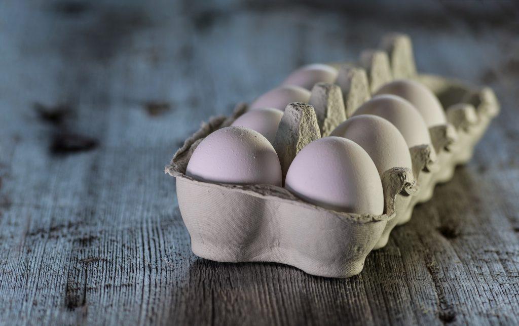 acht weiße eier in pappschachtel auf holztisch