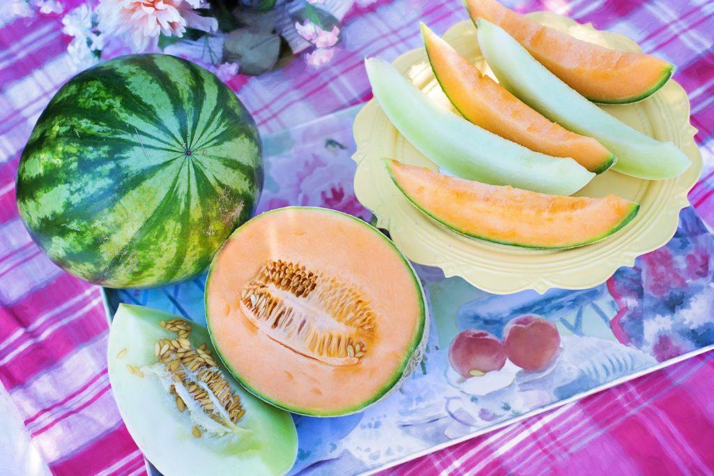 verschiedene Melonen aufgeschnitten auf einem Teller, als halbe und im ganzen auf einem Sommerlichen Tisch