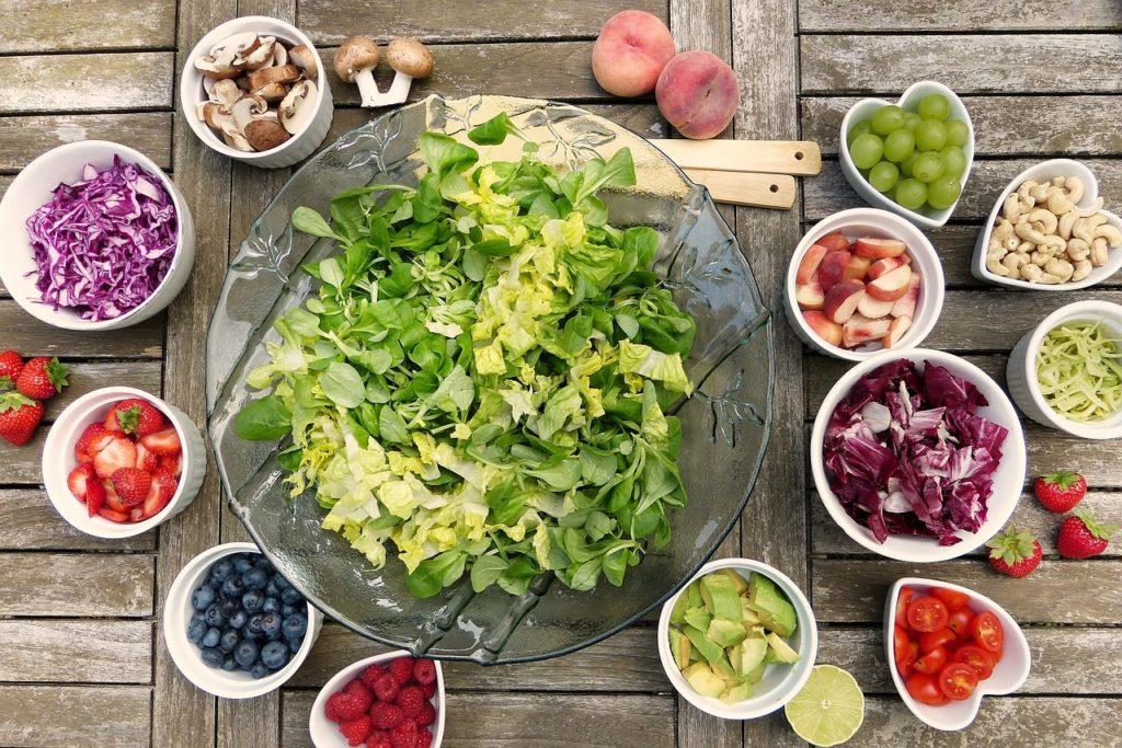 verschiedene Obst und Gemüsesorten in Schälchen und Schüsseln, Felsdalat, Kohl, Blaubeeren, liebevoll angerichtet auf einem alten Holztisch