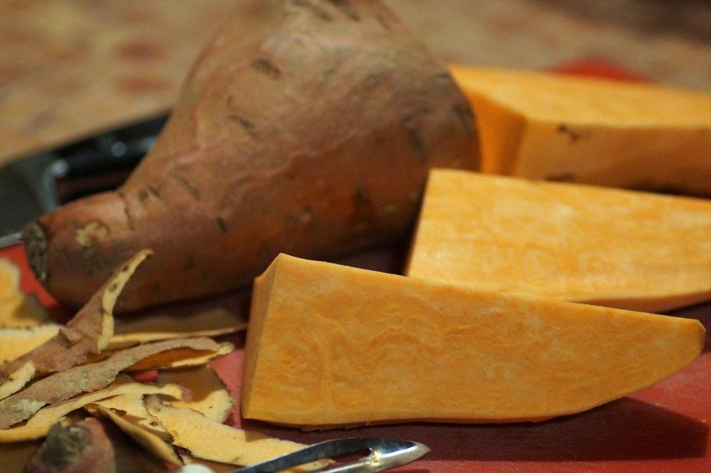 Süßkartoffeln, angeschnitten in dreiecke und eine ganze. schalen nebendran