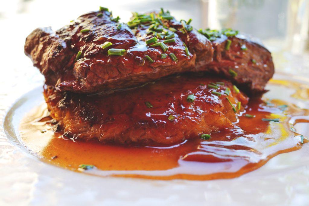 Fleisch mit vegetarischer Bratensoße, auf weißem Teller